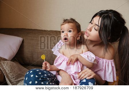Picture of pretty young mother sitting on sofa with her little shocked daughter indoors. Looking aside.
