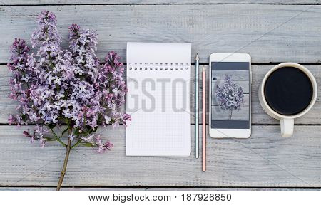 Cup of coffee notepad a lilac branch and phone with the same lilac on the white wooden table