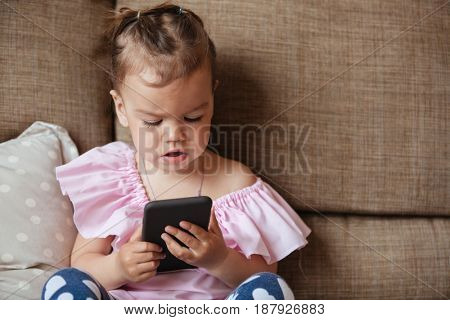 Image of concentrated little girl child sitting on sofa indoors using mobile phone. Looking aside.
