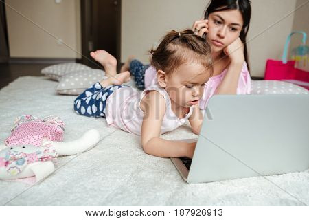 Image of serious young mother talking by phone while her little daughter lies on bed indoors using laptop computer. Looking aside.