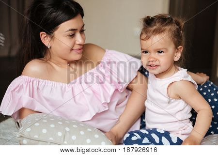 Image of amazing young mother lies on bed with her little daughter indoors. Looking aside.