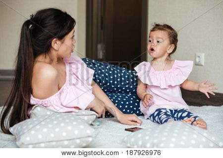 Photo of beautiful young mother with her little daughter lies on bed indoors and talking with each other. Looking aside.
