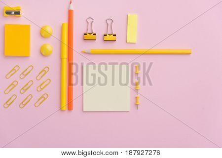 Top view picture of office supplies on the pink background table