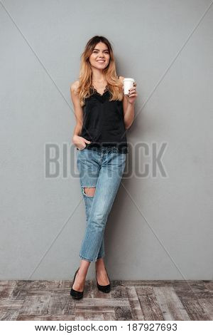 Young blonde lady with cup of coffee posing isolated over grey