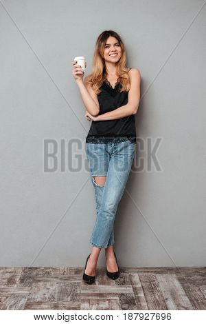 Young blonde lady with cup of coffee posing isolated over grey background