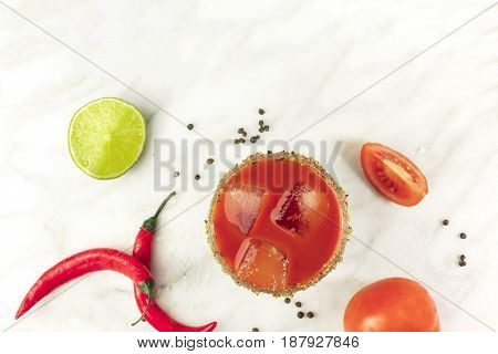 Bloody Mary cocktail, shot from above on a white marble texture, with red hot chili peppers, slices of lime, tomatoes, and copy space