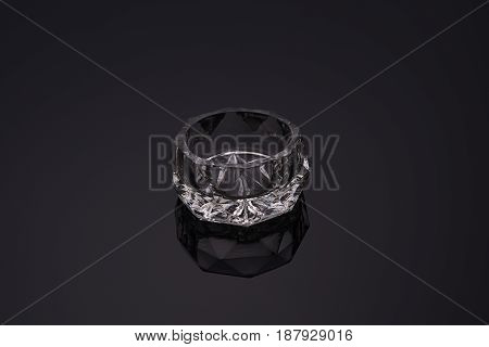 Fragile Czech crystal cut glass ware wedding saltcellar reflected in dark background