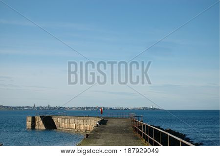 Cairnbulg Harbour in Aberdeenshire, Scotland with a clear sky and blue sea.