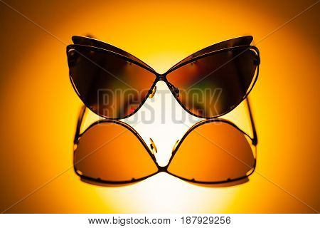 Stylish polarized mirrored sunglasses with metal frame in sunlight with unfocused background
