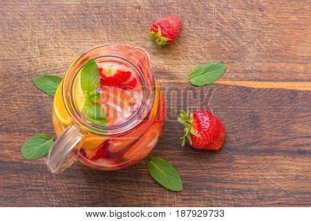 Aromatized Water With Fresh Strawberries With Oranges And Mint In A Glass Jug .