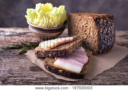 Traditional ukrainian sandwiches made of brown rye bread and smoked lard on a piece of brown paper and natural wooden textured surface with unfocused background. On this photo it is accompanied by green cabbage leaves and rosemary herb.
