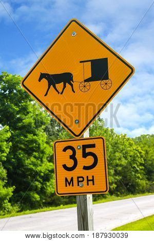 Kingston, WI, USA - 07/ 28/2015: Yellow traffic sign warning vehicle drivers of Amish horse and buggies on the roads and a maximum speed of 35mph
