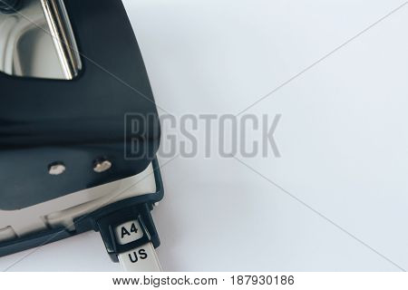 Black and grey office paper hole puncher isolated on white background close-up