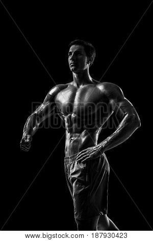 Muscular and fit young bodybuilder fitness male model posing over black background. Studio shot on black background.