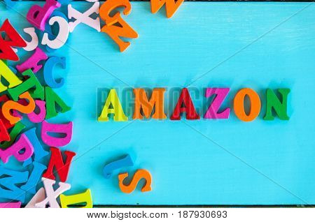 KIEV, UKRAINE - MAY 09, 2017: Amazon - word composed of small colored letters on blue background. Amazon is an American electronic commerce company.