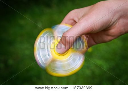 Teen boy with a fidget spinner outdoors