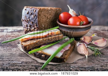 Traditional ukrainian sandwiches made of brown rye bread and smoked lard on a piece of brown paper and natural wooden textured surface with unfocused background. On this photo it is accompanied by green onions tomatoes garlic and rosemary.