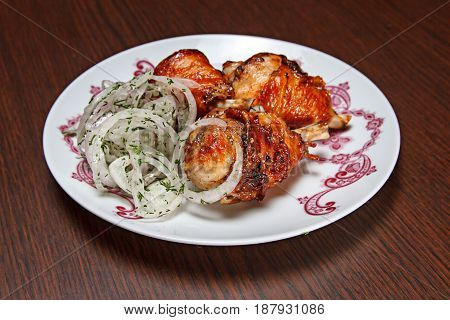 Close up of hot grilled chicken drumsticks with onions rings on wooden background.