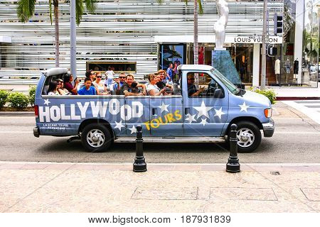 Beverly Hills, CA, USA - 07/01/2015: Hollywood Tours vehicle escorts tourists on a guided tour of where the rich and famous live and shop in Beverly Hills California