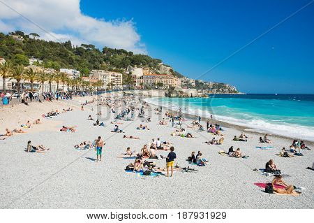 NICE FRANCE - April 22 2017: People sunbathing and relaxing on the beach in Nice France.