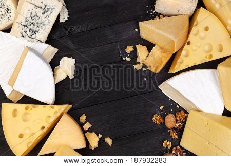 Various types of cheese on black wooden table background. Cheddar, parmesan, emmental, blu cheese. Top view, copy space.