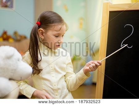 Beautiful Young Girl Is Teaching Toys At Home On Blackboard. Preschool Home Education.