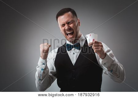 Handsome confident man holding cards looking at camera. Studio shot on gray background. Two Aces. Emotions happy win