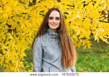 Beautiful young woman in leather jacket and black skirt standing and posing in autumn park. Pretty young woman with long straight brown hair