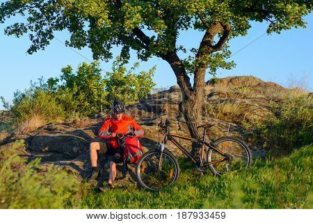 Cyclist in Red Jacket and Helmet Resting near Mountain Bike on the Rocky Hill under Beautiful Green Tree. Adventure and Travel Concept.