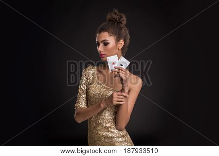 Woman winning - Young woman in a classy gold dress holding two aces, a poker of aces card combination. Studio shot on black background