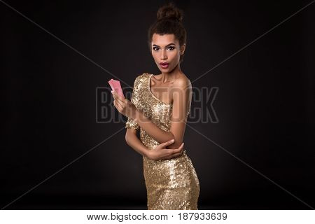Woman winning - Young woman in a classy gold dress holding two cards, a poker of aces card combination. Studio shot on black background. Emotions