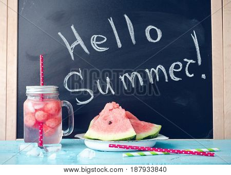 Hello summer written on the blackboard with drink in glass mason jar with slices of watermelon and ice on blue background. Fresh fruit flavored infused detox water. Start Summer Concept.