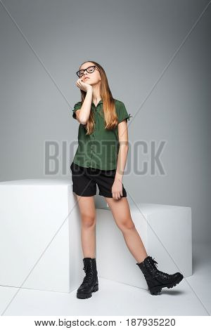Portrait of young cute spectacled girl over gray background. woman dressed in green T-shirt, black shorts and boots