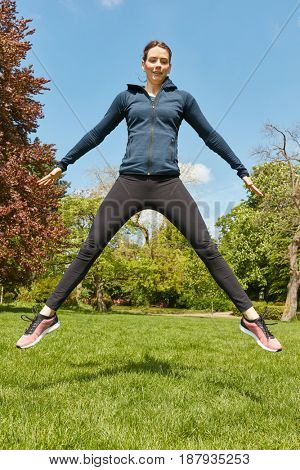 Sporty woman jumping in the park as crossfit training