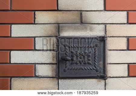 New brown brick wall with rusty door furnace. Abstract. Pattern.