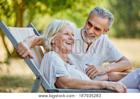 Senior couple laughing sitting on a deck chair in summer in the nature