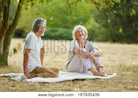 Happy senior citizens flirting in the park on a date in the park in summer