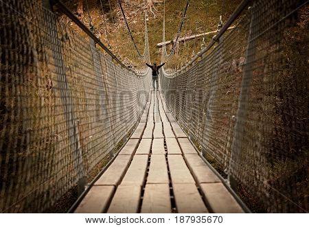 man walking over a rope bridge across a deep ravine. sepia toned