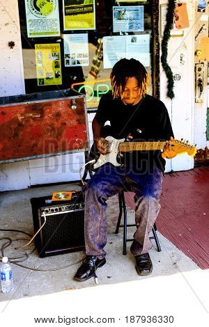 Clarksdale, MS, USA - 06/10/2015: Black young man playing his guitar and singing the blues in Clarksdale Mississippi