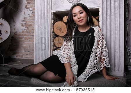 Asian girl in torn pantyhose sitting near the fireplace with the shawl on his shoulders.