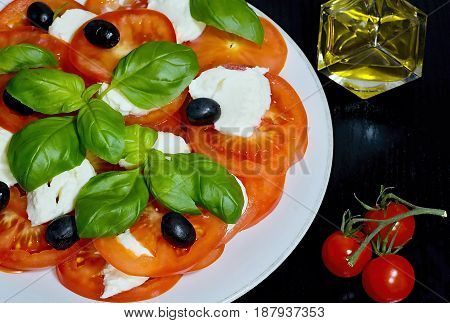 Caprese salad. Classic caprese salad. Italian traditional caprese salad ingredients. Mediterranean food. Caprese salad Tomato and mozzarella with basil leaves on wooden background.