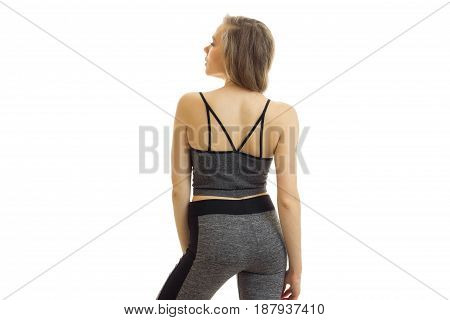 Slim athletic girl in grey top and trousers with beautiful buttocks looking up and stands with his back to the camera isolated on white background