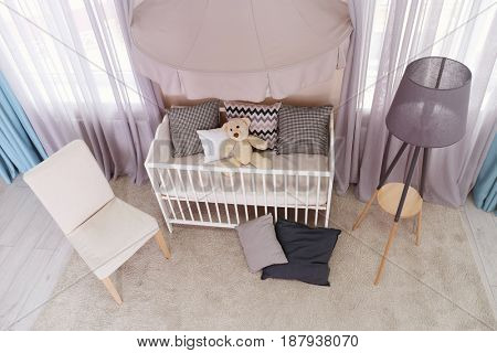 Interior of light baby room with furniture and tripod floor lamp