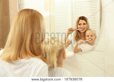 Young mother with her daughter brushing teeth and looking in mirror
