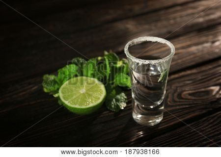 Tequila shot with juicy lime and salt on wooden background