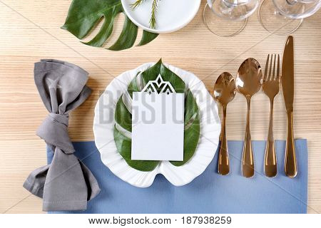 Table setting with lilac color napkin, blank card and floral decor on wooden surface