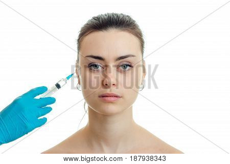 cosmetologist makes injection syringe on the face of a young beautiful girl who looks straight close-up isolated on white background