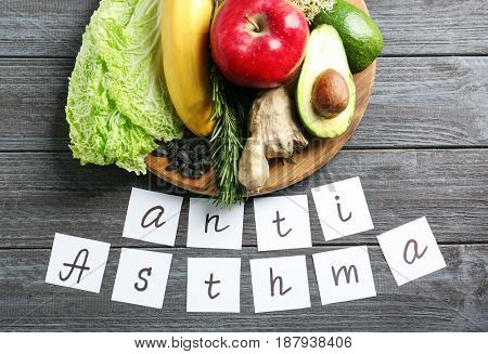 Text ANTI ASTHMA and set of products on wooden background