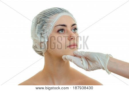young cute girl in medical hair hat came to the beautician and he looks at her face in white glove isolated on white background