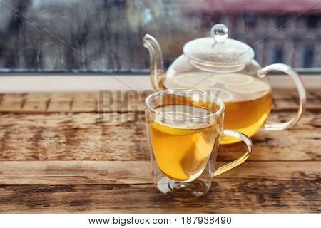 Glass cup of hot tasty drink with teapot on wooden windowsill